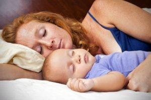 Vauva nukkuu äidin vieressä