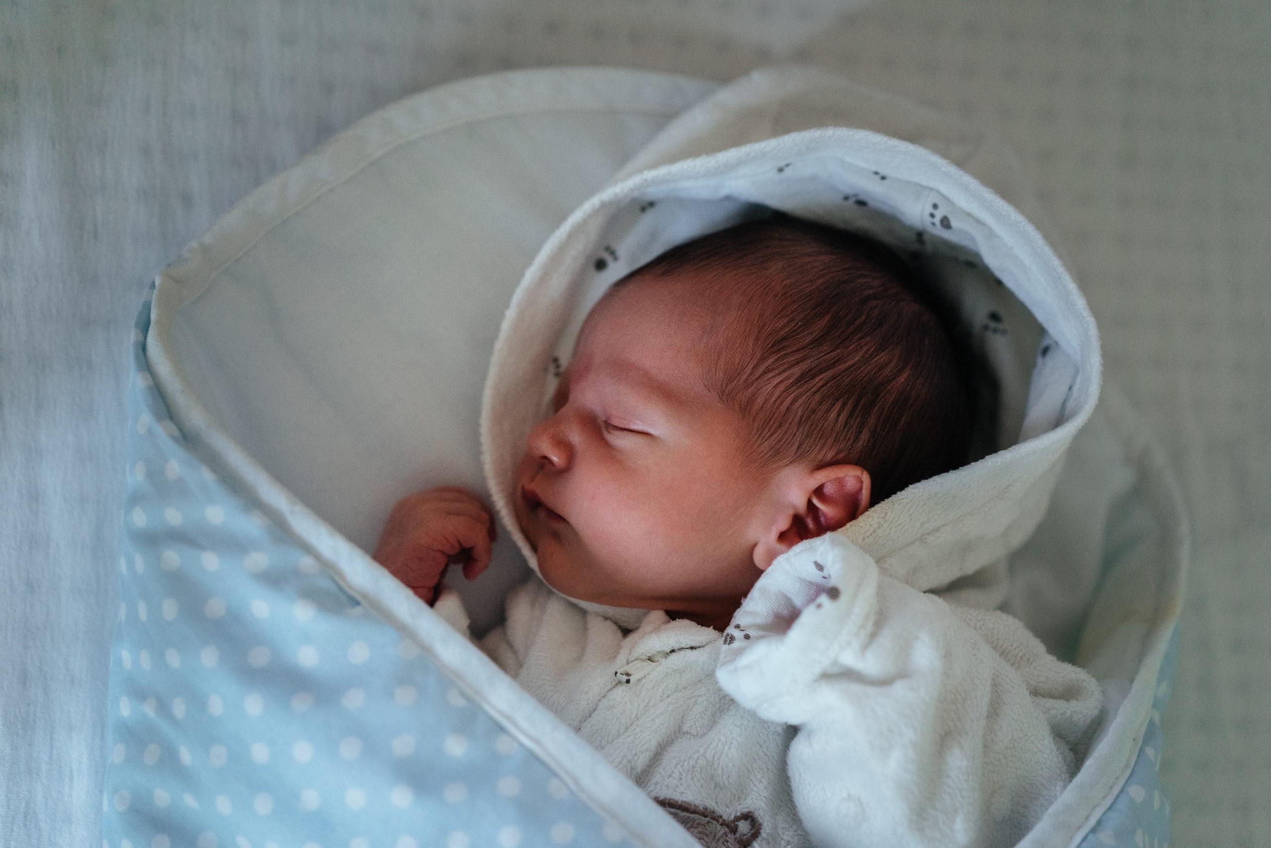 Vastasyntynyt vauva nukkuu kapaloituna